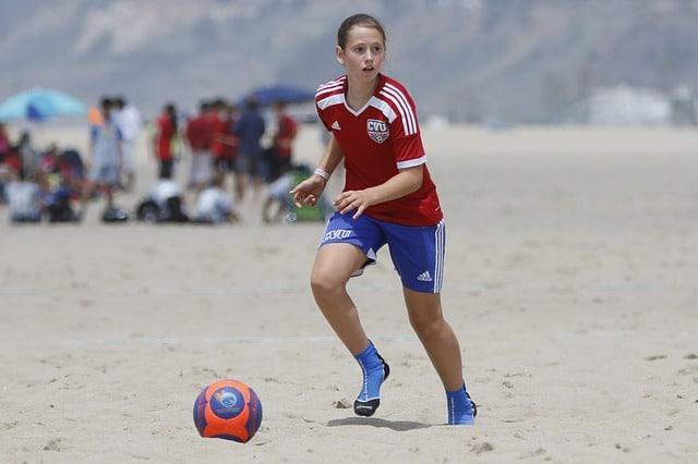 femme qui joue au foot sur la plage