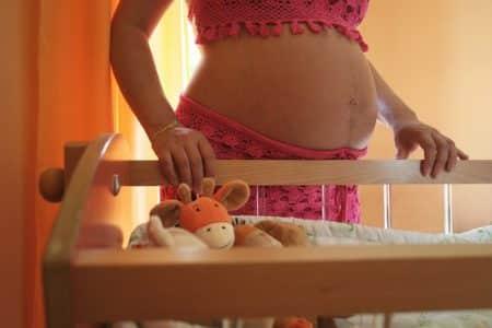 femme enceinte à coté d'un berceau